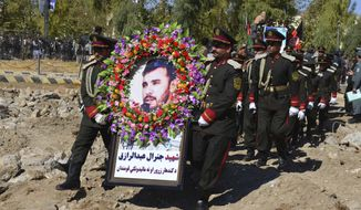 Guards of honor carry a photo of Gen. Abdul Raziq, Kandahar police chief, who was killed by a guard, during his burial ceremony in Kandahar, Afghanistan, Friday, Oct. 19, 2018. Afghanistan's election commission on Friday postponed elections in Kandahar for a week, following a brazen attack on a high-profile security meeting there with a U.S. delegation that killed at least two senior provincial officials, including the province's police chief. (AP Photo)