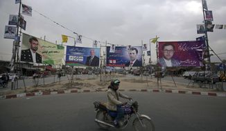 In this Tuesday, Oct. 16, 2018, photo, a man rides his motorbike in front of campaign posters for parliamentary candidates, in Kabul, Afghanistan. Afghans will return to the polls on Saturday, hoping to bring change to a corrupt government that has lost nearly half the country to the Taliban. In the eight years since Afghanistan last held parliamentary elections a resurgent Taliban has carried out near-daily attacks, seizing large swathes of the countryside and threatening major cities. (AP Photo/Rahmat Gul)