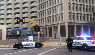 FILE - In this Dec. 11, 2015 file photo, police gather outside of City Hall while searching for a gunman in Albuquerque, N.M. Albuquerque police on Thursday, Oct. 18, 2018, announced the hiring of a law enforcement veteran to manage a unit for dispatchers and real-time crime analysts who was accused decades ago in a lawsuit of using excessive force during a traffic stop. (AP Photo/Mary Hudetz, File)