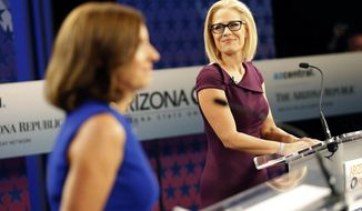 U.S. Senate candidates, U.S. Rep. Martha McSally, R-Ariz., left, and U.S. Rep. Kyrsten Sinema, D-Ariz., prepare their remarks in a television studio prior to a televised debate, Monday, Oct. 15, 2018, in Phoenix. (AP Photo/Matt York)