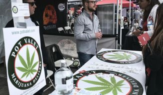 FILE - This March 31, 2018 photo shows a booth advertising a delivery service for cannabis at the Four Twenty Games in Santa Monica, Calif. California is moving a step closer to allowing marijuana deliveries in communities that have banned retail sales. Regulators on Friday, Oct. 19, 2018, announced preliminary approval of the proposed rule over objections from cities and police chiefs who say the policy will lead to crime. (AP Photo/Richard Vogel, File)
