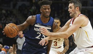 Minnesota Timberwolves' Jimmy Butler, left, drives around Cleveland Cavaliers' Kevin Love in the first half of an NBA basketball game Friday, Oct. 19, 2018, in Minneapolis. (AP Photo/Jim Mone)