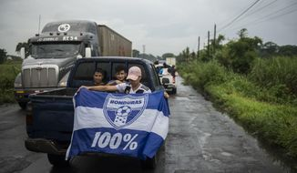 A Honduran migrant holds a Honduras national flag, as he sits in the bed of a  a pick-up truck, on his way to the Mexican border, in Cocales, about 80 miles north-west from Guatemala City, Guatemala, Thursday, Oct. 18, 2018. Many of the more than 2,000 Hondurans in a migrant caravan trying to wend its way to the United States left spontaneously with little more than the clothes on their backs and what they could quickly throw into backpacks. (AP Photo/ Oliver de Ros)