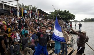 Hundreds of Honduran migrants stand at the shore of the Suchiate river on the border between Guatemala and Mexico, in Tecun Uman, Guatemala, Thursday, Oct. 18, 2018. Mexico's foreign ministry says government officials at its southern border with Guatemala have started assisting the early arrivals from a caravan of some 3,000 Honduran migrants that has drawn sharp criticism from U.S. President Donald Trump. (AP Photo)