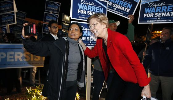 Sen. Elizabeth Warren poses for a selfie while greeting supporters before a debate with her Republican opponent Geoff Diehl in Boston, Friday, Oct. 19, 2018. (AP Photo/Michael Dwyer)