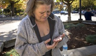 This photo taken Oct. 11, 2018, shows Adrienne Wurts looking at her scarred hands as she tells the story of the day she was attacked and stabbed by David Dario Lucius outside the Walton Post Office last month. Wurts was outside the Lane County Courthouse in Eugene. (Andy Nelson/The Register-Guard via AP)