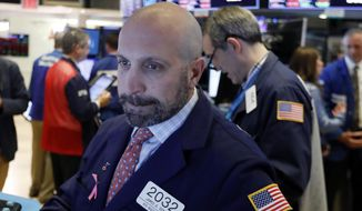 FILE- In this Oct. 11, 2018, file photo specialist James Denaro works at his post on the floor of the New York Stock Exchange. The U.S. stock market opens at 9:30 a.m. EDT on Friday, Oct. 19. (AP Photo/Richard Drew, File)