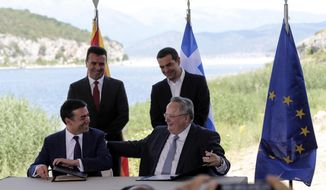 FILE - In this Sunday, June 17, 2018, file photo, Greek Prime Minister Alexis Tsipras, background right, and his Macedonian counterpart Zoran Zaev, background left, look on as Greek Foreign Minister Nikos Kotzias, right, and his Macedonian counterpart Nikola Dimitrov sign an agreement on Macedonia's new name in the village of Psarades, Prespes Greece. Greek Foreign Minister Nikos Kotzias resigned Wednesday, Oct. 17, 2018, following a disagreement with the defense minister over the handling of a recent deal which would change Macedonia's name in exchange for Greece dropping its objections to the country joining NATO. (AP Photo/Yorgos Karahalis, File)