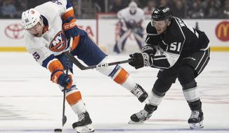 New York Islanders defenseman Johnny Boychuk, left, shoots past Los Angeles Kings left wing Austin Wagner in the first period of an NHL hockey game Thursday, Oct. 18, 2018 in Los Angeles. (AP Photo/Kyusung Gong)