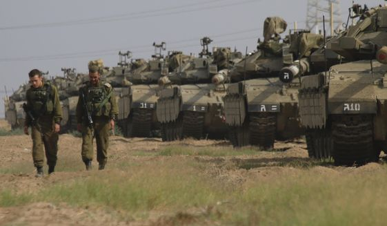 Israeli soldiers walk past tanks in a gathering point near Israel Gaza border, Friday, Oct. 19, 2018. (AP Photo/Ariel Schalit)