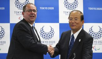 Xavier Gonzalez, left, CEO of the International Paralympic Committee (IPC), and Toshiro Muto, right, CEO of the Tokyo Organizing Committee of the Olympic and Paralympic Games (Tokyo 2020) shake hands after their IPC and Tokyo 2020 joint press conference in Tokyo, Friday, Oct. 19, 2018. (AP Photo/Eugene Hoshiko)