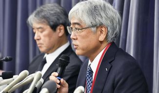 "KYB Corp. Senior Managing Executive Officer Keisuke Saito, right, speaks during a press conference in Tokyo Friday, Oct. 19, 2018. The Japanese government has ordered the company that falsified quality data for earthquake ""shock absorbers"" used in hundreds of buildings to speed up an investigation and fix any problems quickly. (Yu Nakajima/Kyodo News via AP)"
