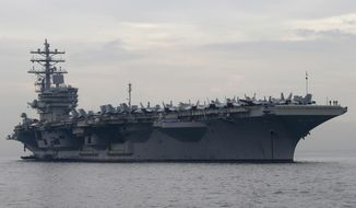 In this June 26, 2018, file photo, the U.S. aircraft carrier USS Ronald Reagan anchors off Manila Bay for a goodwill visit in Manila, Philippines. An U.S. Navy helicopter has crashed on the flight deck of the aircraft carrier USS Ronald Reagan Friday, Oct. 19, 2018, causing non-fatal injuries to sailors. (AP Photo/Bullit Marquez, File)