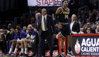 Denver Nuggets' Gary Harris (14) leaps in front of Los Angeles Clippers head coach Doc Rivers, center, after Harris made a basket late in the fourth quarter of an NBA basketball game Wednesday, Oct. 17, 2018, in Los Angeles. (AP Photo/Marcio Jose Sanchez)