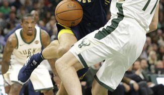 Indiana Pacers forward Bojan Bogdanovic loses control of the ball as he collides with Milwaukee Bucks forward Ersan Ilyasova as he drives to the basket during the first half of an NBA basketball game Friday, Oct. 19, 2018, in Milwaukee. (AP Photo/Mike Roemer)