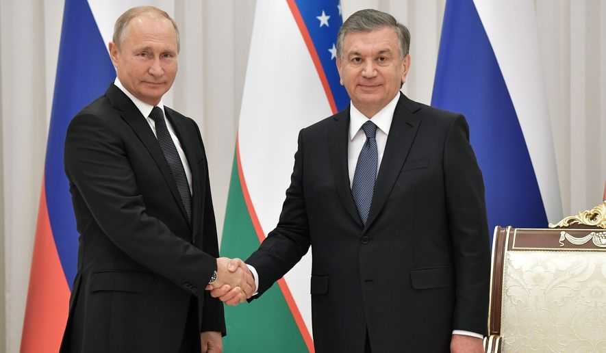 Russian President Vladimir Putin, left, and Uzbek President Shavkat Mirziyoyev shake hands during their meeting in Tashkent, Uzbekistan, on Friday, Oct. 19, 2018. Putin arrived in Uzbekistan on Friday for an official visit. (Alexei Nikolsky, Sputnik, Kremlin Pool Photo via AP)