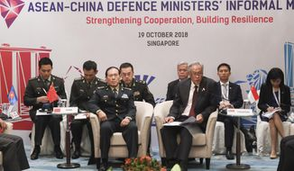 Chinese Defense Minister Wei Fenghe, center left, and Singapore Defense Minister Ng Eng Hen, center right, chair the ASEAN-China Defense Ministers' Informal Meeting during the 12th ASEAN Defense Ministers' Meeting in Singapore Friday, Oct. 19, 2018. (AP Photo/Don Wong)