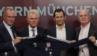 """FILE - In this Monday, Oct. 9, 2017 file photo, Bayern Munich's new coach Jupp Heynckes, second left, is flanked by the club's CEO Karl-Heinz Rummenigge, left, president Uli Hoeness, right, and sports director Hasan Salihamidzic, second right, during his presentation at a news conference in Munich, Germany. German soccer giant Bayern Munich has hit out against the media for what it calls """"derogatory, slanderous reporting"""" of the club's recent struggles _ and even threatened to take legal action. Bayern's chairman Karl-Heinz Rummenigge, president Uli Hoeness and sport director Hasan Salihamidzic appeared at a joint press conference on Friday, Oct. 19, 2018 speaking out against what they deem to be unfavorable coverage after four games without a win. (AP Photo/Matthias Schrader, file)"""