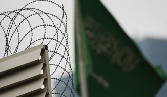 Behind barbed wire, Saudi Arabia's flag flies atop the country's consulate in Istanbul, Thursday, Oct. 18, 2018. Turkish crime-scene investigators finished an overnight search of both residence and a second search of the consulate itself amid Ankara's fears that Saudi writer Jamal Khashoggi was killed and dismembered inside the diplomatic mission in Istanbul. (AP Photo/Lefteris Pitarakis)