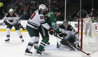 Minnesota Wild defenseman Ryan Suter (20) pressures Dallas Stars center Jason Spezza (90) whotries to control the puck as goalie Devan Dubnyk (40) protects the goal and center Mikko Koivu, right, watches during the first period of an NHL hockey game, Friday, Oct. 19, 2018, in Dallas. (AP Photo/Mike Stone)