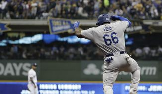 Los Angeles Dodgers' Yasiel Puig reacts after hitting a three-run home run during the sixth inning of Game 7 of the National League Championship Series baseball game against the Milwaukee Brewers Saturday, Oct. 20, 2018, in Milwaukee. (AP Photo/Matt Slocum)