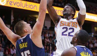 Phoenix Suns center Deandre Ayton (22) shoots over Denver Nuggets center Nikola Jokic (15) and Paul Millsap (4) during the first quarter of an NBA basketball game, Saturday, Oct. 20, 2018, in Denver. (AP Photo/Jack Dempsey)