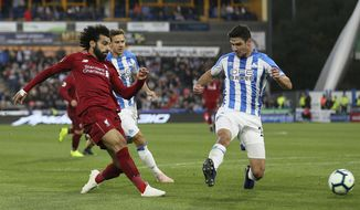 Liverpool's Mohamed Salah, left, scores his side's first goal of the game against Huddersfield Town during their English Premier League soccer match at the John Smith's Stadium in Huddersfield, England, Saturday Oct. 20, 2018. (Richard Sellers/PA via AP)