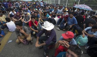 Central American migrants sit on the bridge over the Suchiate River that separates Guatemala and Mexico, in Tecun Uman, Guatemala, Friday, Oct. 19, 2018. Central Americans traveling in a mass caravan broke through a Guatemalan border fence and streamed by the thousands toward Mexican territory, defying Mexican authorities' entreaties for an orderly migration and U.S. President Donald Trump's threats of retaliation. (AP Photo/Moises Castillo)