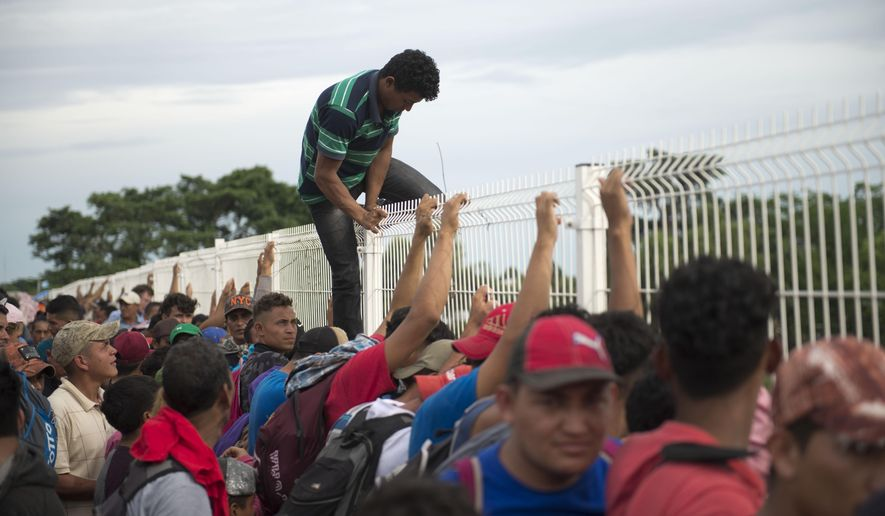 A migrant tired of waiting to cross into Mexico, climbs a border bridge fence to jump into the Suchiate River, in Tecun Uman, Guatemala, Friday, Oct. 19, 2018. Some of the migrants traveling in a mass caravan towards the U.S.-Mexico border organized a rope brigade to ford its muddy waters. (AP Photo/Oliver de Ros)