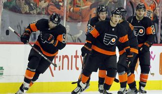 Philadelphia Flyers' Jakub Voracek, left, skates ahead of his teammates after celebrating his goal that broke the tie in the third period of an NHL hockey game, against New Jersey Devils, Saturday, Oct. 20, 2018, in Philadelphia. The Flyers won 5-2. (AP Photo/Tom Mihalek)