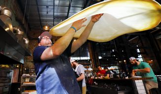 """Goodfellas Pizzeria general manager Sean Lindsey, of Lexington, Ky., tosses pizza dough at Goodfellas in the Distillery District in Lexington, Ky., Tuesday, Oct. 9, 2018. Goodfellas fans have shown their support following a review from Barstool Sports founder Dave Portnoy giving Goodfellas Pizzeria in the Distillery District a """"0.0"""" rating after he said his slice was """"ice cold.""""  (Alex Slitz/Lexington Herald-Leader via AP)"""