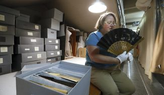 "Holding a Japanese hand fan Christina Kastell, curator of history and anthropology at the Putnam Museum talks about ""fan language"". By holding the fan in a certain way, a woman could silently communicate across a room.   (Andy Abeyta/Quad City Times via AP)"