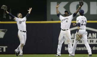 Milwaukee Brewers' Ryan Braun, Christian Yelich and Lorenzo Cain celebrate after Game 6 of the National League Championship Series baseball game against the Los Angeles Dodgers Friday, Oct. 19, 2018, in Milwaukee. The Brewers won 7-2 to tie the series at 3-3. (AP Photo/Matt Slocum)
