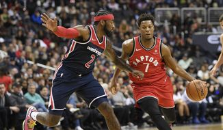 Toronto Raptors guard Kyle Lowry (7) dribbles the ball against Washington Wizards guard John Wall (2) during the first half of an NBA basketball game, Saturday, Oct. 20, 2018, in Washington. (AP Photo/Nick Wass)