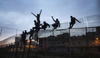 FILE - In this Friday, March 28, 2014, file photo, Sub-Saharan migrants climb over a metallic fence that divides Morocco and the Spanish enclave of Melilla. Since the early 1990s, Spain has built six-meter (20-foot) layered border fences around its two North African enclaves, Ceuta and Melilla, to help dissuade migrants, now mostly from sub-Saharan countries, from entering the cities from Morocco in the hope of reaching a better a life in Europe. (AP Photo/Santi Palacios, File)