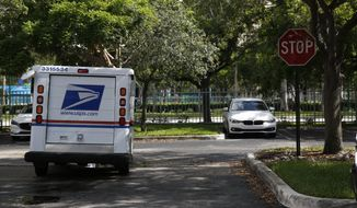 A mail carrier for the United States Postal Service drives away after delivering mail to an apartment complex on Thursday, June 14, 2018, in Aventura, Fla. (AP Photo/Brynn Anderson)