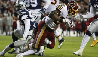 Washington Redskins running back Adrian Peterson (26) carries the ball during the second half of an NFL football game between the Washington Redskins and the Dallas Cowboys, Sunday, Oct. 21, 2018 in Landover, Md. (AP Photo/Alex Brandon)
