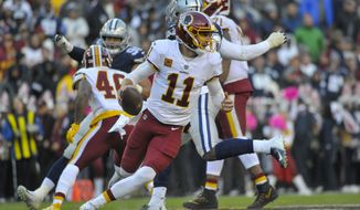 Washington Redskins quarterback Alex Smith (11) scrambles with the ball during the first half of an NFL football game between the Washington Redskins and the Dallas Cowboys, Sunday, Oct. 21, 2018 in Landover, Md. (AP Photo/Mark Tenally)