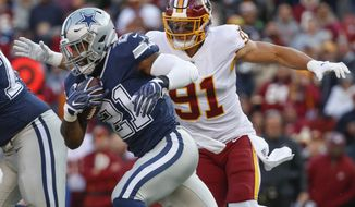 Dallas Cowboys running back Ezekiel Elliott (21) carries the ball past Washington Redskins linebacker Ryan Kerrigan (91) during the first half of an NFL football game between the Washington Redskins and the Dallas Cowboys, Sunday, Oct. 21, 2018 in Landover, Md. (AP Photo/Alex Brandon)