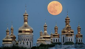 In this May 4, 2004, photo, a full moon rises above the golden domes of the Orthodox Monastery of the Caves in Kiev, Ukraine. Tensions over the imminent formation of a Ukrainian Orthodox church independent of Moscow are raising fears that nationalists will try to seize Russian church properties.(AP Photo/Efrem Lukatsky, File)