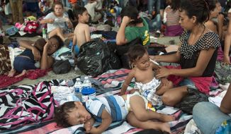 A group of migrants rests at the central park in Ciudad Hidalgo, Mexico, Saturday, Oct. 20, 2018. About 2,000 Central American migrants who circumvented Mexican police at a border bridge and swam, forded and floated across the river from Guatemala decided on Saturday to re-form their mass caravan and continue their trek northward toward the United States. (AP Photo/Oliver de Ros)
