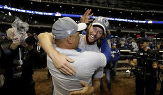Los Angeles Dodgers' Clayton Kershaw celebrates with manager Dave Roberts after winning Game 7 of the National League Championship Series baseball game against the Milwaukee Brewers Saturday, Oct. 20, 2018, in Milwaukee. The Dodgers won 5-1. (AP Photo/Matt Slocum)