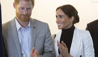 Britain's Prince Harry and his wife Meghan, Duchess of Sussex, clap duirng a lunchtime reception hosted by Australian Prime Minister Scott Morrison with Invictus Games competitors, their families and friends in Sydney Sunday, Oct. 21, 2018. (Paul Edwards/Pool Photo via AP)