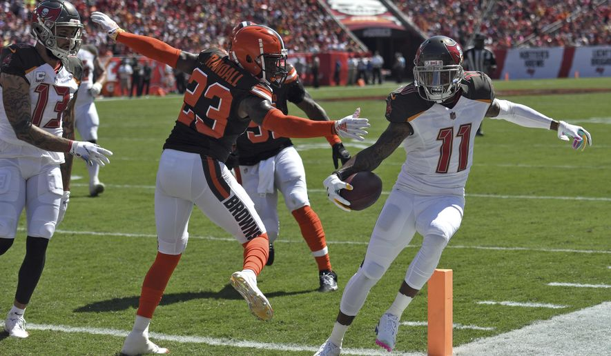 Tampa Bay Buccaneers wide receiver DeSean Jackson (11) steps around Cleveland Browns strong safety Damarious Randall (23) on an 11-yard touchdown run during the first half of an NFL football game Sunday, Oct. 21, 2018, in Tampa, Fla. (AP Photo/Jason Behnken)
