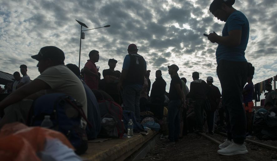 Honduras migrants stand on the bridge that stretches over the Suchiate River, connecting Guatemala and Mexico, as they wait to be attended by Mexican migration authorities in Tecun Uman, Guatemala, Sunday, Oct. 21, 2018. Despite Mexican efforts to stop them at the border, about 5,000 Central American migrants resumed their advance toward the U.S. border early Sunday in southern Mexico. (AP Photo/Oliver de Ros)