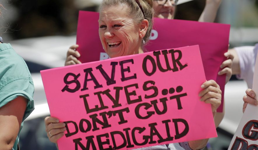 In this June 27, 2017, photo, protesters block a street during a demonstration against the Republican bill in the U.S. Senate to replace former President Barack Obama's health care law, in Salt Lake City. (AP Photo/Rick Bowmer) **FILE**