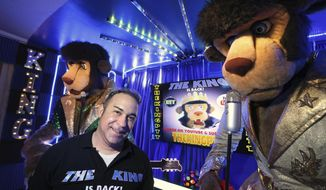 Jared Sanchez, center, poses with The King, left, and King Puff, right, in his Tampa home Monday, Sept. 17, 2018. Sanchez is so obsessed with the 10-foot tall animatronic lions that sang Elvis tunes in Chuck E. Cheese's restaurants, he now owns four. 'I don't hoard, I restore,' he said jokingly during a recent tour. Sanchez converted a master bedroom of his home into a studio and now films the lions singing parody songs and posts them to YouTube.  (James Borchuck/Tampa Bay Times via AP)