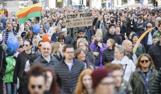 """People attend a demonstration called """"heart instead of hounding"""" to protest against a far right PEGIDA demonstration in Dresden, eastern Germany, Sunday, Oct.21, 2018. (Oliver Killig/dpa via AP)"""