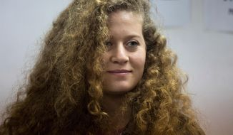 FILE - In this Tuesday, Feb. 13, 2018 file photo, Palestinian activist Ahed Tamimi stands inside the Ofer military prison near Jerusalem. When Israel locked up Ahed Tamimi for slapping a soldier last year, it hoped to finally silence the teenage Palestinian activist. Instead, it created an international celebrity. (AP Photo/Ariel Schalit, File)