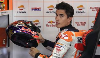 Spain's rider Marc Marquez takes up a helmet in the pits during the MotoGP Japanese Motorcycle Grand Prix at the Twin Ring Motegi circuit in Motegi, north of Tokyo, Sunday, Oct. 21, 2018. (AP Photo/Shizuo Kambayashi)